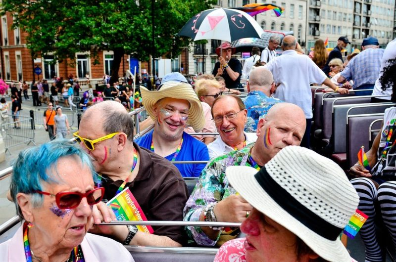 Photograph of Opening Doors charity enjoying Pride parade on an open top bus. Lots of colour and rainbows and happy people.